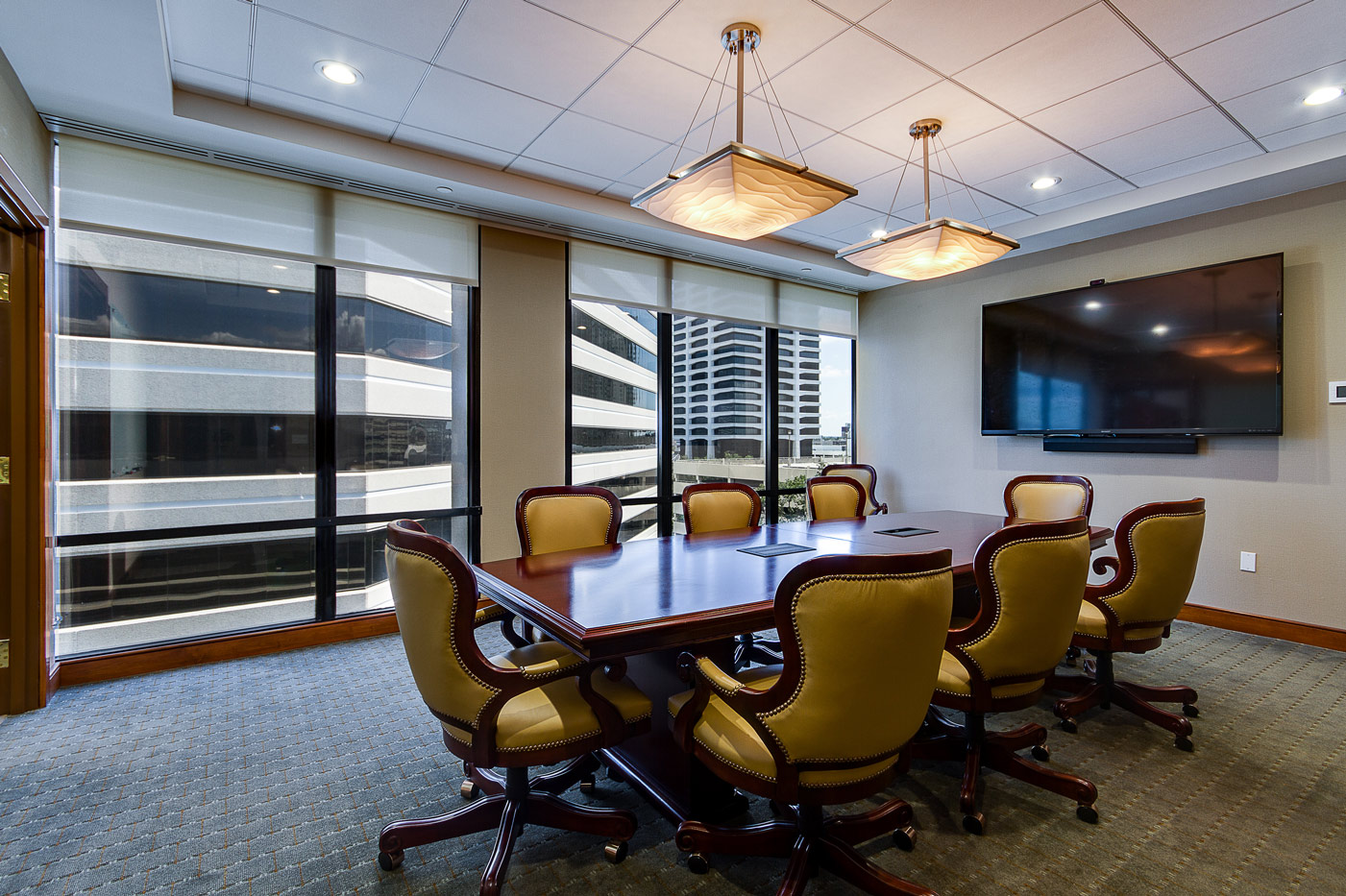 conference room with tables chairs and large screen